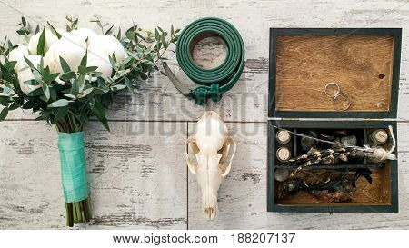 Top view of green groom's belt skull wedding bouquet of white peony wooden box with wedding rings bird's paws feathers empty bottles and stones on wooden background