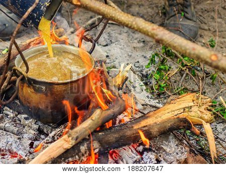 Cooking in a hike in a metal kettle on fire croup poured into boiling broth