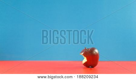 Red apple with missing a bite on background colorful. Copyspace