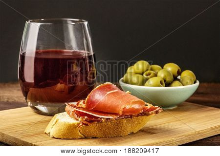 A photo of a jamon tapa, a piece of cured ham on a slice of bread, with a glass of red wine and green olives, on a dark background with a place for text