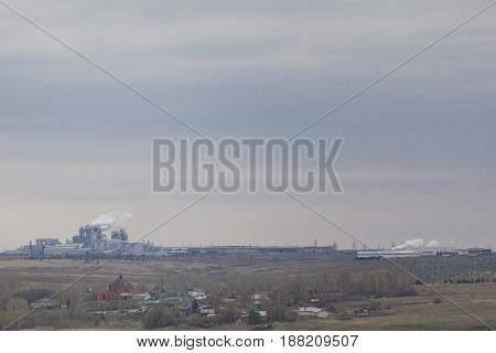 Views of the industrial plant near the village under a grey autumn sky