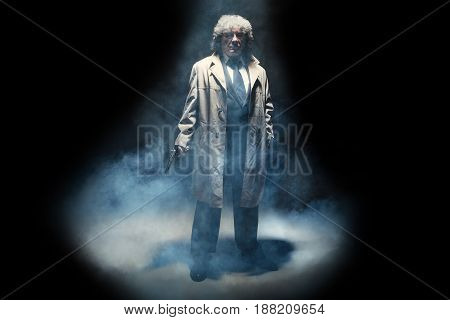 Senior police agent with a gun standing as detective or mafia boss. Studio shot on gray in retro stile in the light and smoke ray