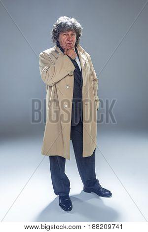 The senior man in cloak as detective or mafia boss. Studio shot on gray in retro stile