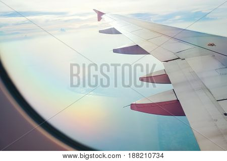 View From Airplane Window. Wing Of An Airplane Flying Above The Clouds