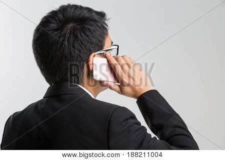 Business concept : Asian handsome businessman smiling and talking on smartphone on white background
