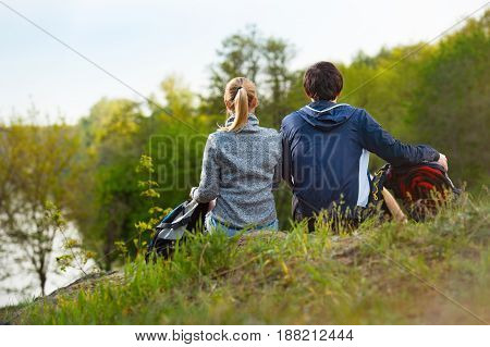 couple of hikers with backpacks looking at a beautiful river and forest. Back view. Travel vacation holidays and adventure concept.