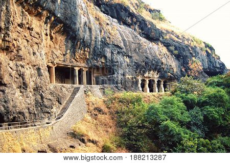 Stairs into the one of Ellora Caves. Entryways with carved columns. Aged photo. Complexes of the rock-cut monastery-temple caves in Maharashtra India.
