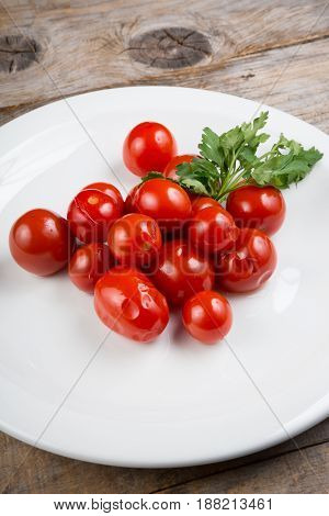 Canned cherry tomatoes served on a white plate