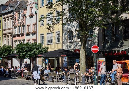 DUESSELDORF, GERMANY - AUGUST 17, 2016: People enjoy food and drinks at a historic Altstadt facade with the Glockenspiel