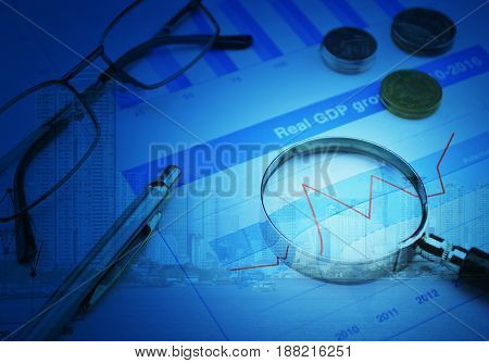 Magnifying glass with growth graph over modern city tower Business success concept