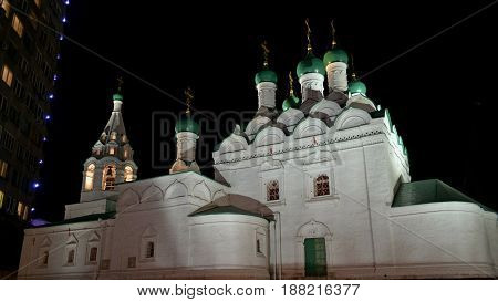 White Church with green domes on the background of a modern building symbolizes the continuity of generations.