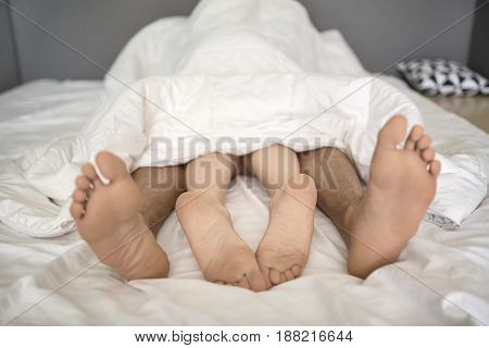 Lovers under the white blanket on the bed. Their barefoot legs are sticking out the blanket. Indoors. Closeup. Horizontal.