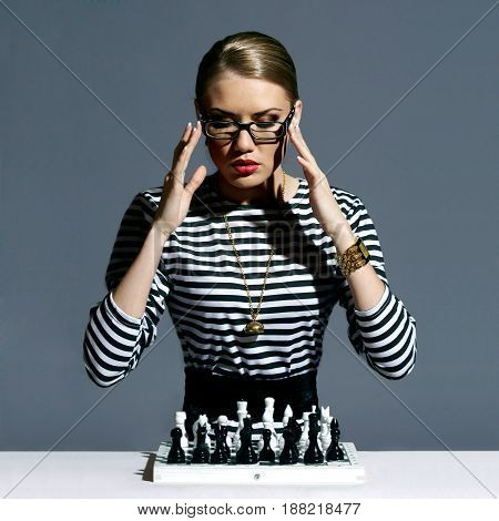 Vogue style fashion portrait of young pretty stylish girl or female model sitting with chess and thinking. Fashionable woman in striped blouse or frock