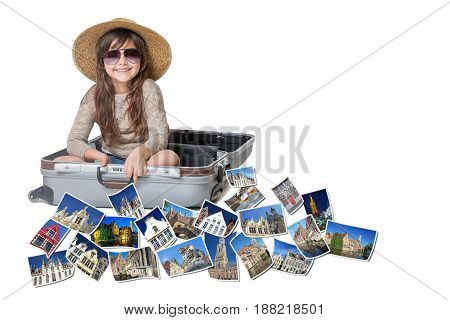 Long haired little girl with straw hat is sitting in a open suitcase. Photos of the sights of Bruges (Flanders Belgium) flies around the suitcase. All is on the white background. Horizontally.