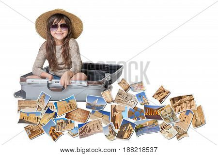 Long haired little girl with straw hat is sitting in a open suitcase. Photos of the sights of Egypt flies around the suitcase. All is on the white background. Horizontally.