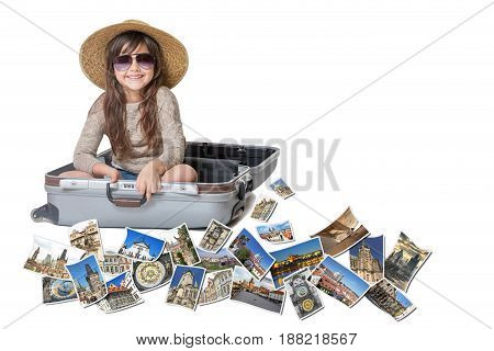 Long haired little girl with straw hat is sitting in a open suitcase. Photos of the sights of Prague (Czech Republic) flies around the suitcase. All is on the white background. Horizontally.