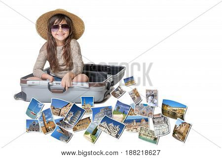 Long haired little girl with straw hat is sitting in a open suitcase. Photos of the sights of Tuscany (Italy) flies around the suitcase. All is on the white background. Horizontally.