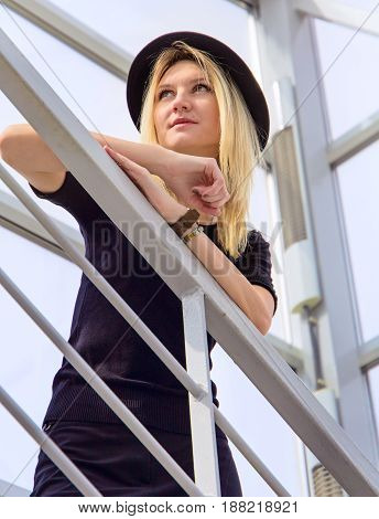 Beautiful young girl in black hat and stands on the metal stairs on the gray background
