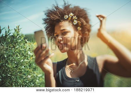 Tilt-shift shooting of cute young mixed female with chamomile wreath using surface of her smart phone as mirror to fix her curly hair afro american teenage female making selfie on her cell telephone