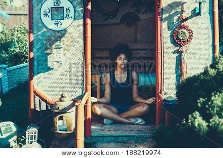 Young charming black girl is sitting cross-legged in Chinese pagoda and practicing relaxing yoga exercises cute curly afro american teenage female enjoying her leisure inside of small asian shack