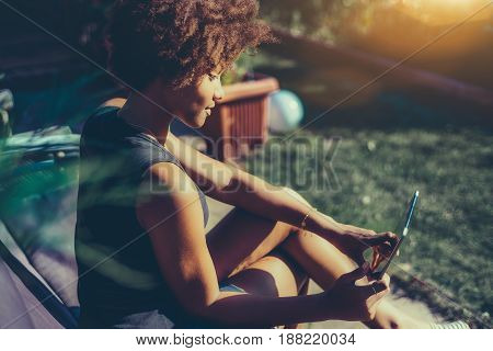 Side view of young afro american girl sitting in park bench and talking with her boyfriend via digital tablet curly mixed teenage female is reading electronic book in sunny summer garden