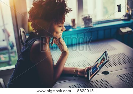 Laughing cute young black girl with perfect smile and dimples sitting at the kitchen table of summer house and making selfies to online chat with her friend using frontal camera of digital tablet