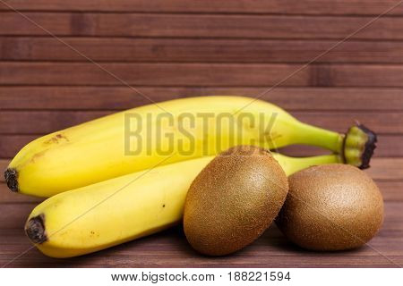 Fresh fruit banana and kiwi isolated on wooden background. Healthy food. A mix of fresh fruit. Group of citrus fruits. Vegetarian raw fruit. Nutrition for a healthy lifestyle.