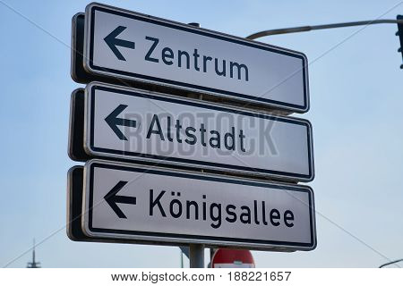 DUESSELDORF, GERMANY - AUGUST 17, 2016: Traffic signs show the right direction to Duesseldorf downtown, Altstadt, and famous shopping street Koenigsallee