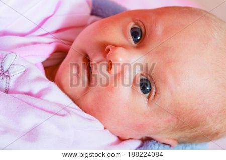 Newborn Baby Lying In Pyjamas And Towel
