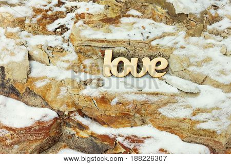 Wooden love sign on stone rock background with snow. Love concept