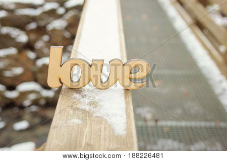 Abstract wooden love sign on wooden texture with snow