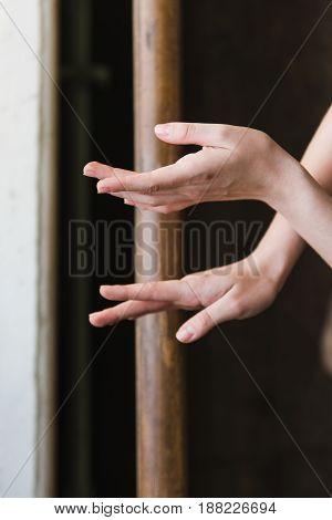 Hands of a ballerina close-up on ballet barre. Top shot.