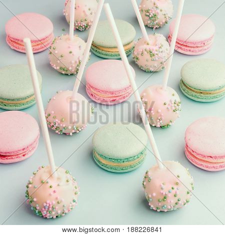 Close-up of colorful macaroons mixed with cake pops with icing on sticks