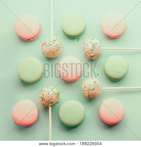 Colorful macaroons mixed with cake crumbs with icing on sticks. Top view. Flat lay.