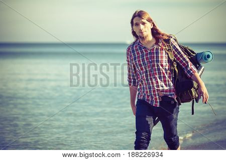 Man hiker backpacker walking with backpack on sea shore at sunny day. Adventure summer tourism active lifestyle. Young long haired guy tramping