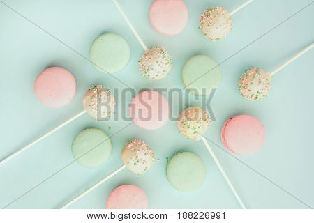 Flat lay of colorful macaroons with cake pops on sticks