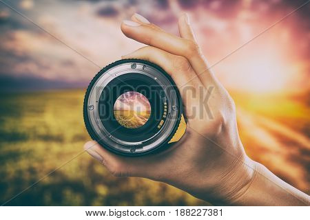 Shown Camera lens for cameras. Sunset on the background of the landscape.