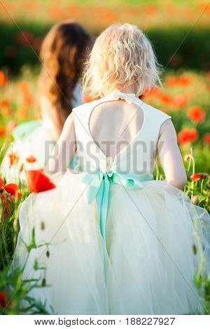 childcare, freedom, countryside, fashion, style concept - sorrounded by tall poppy flowers two fair and dark haired girls, wearing sunday outfits, walking through the field