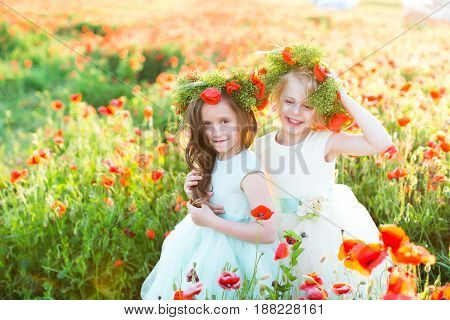 fashion, freedom, journey, travel, family, friendship concept - in the middle of poppy field there are enchanting little nymphs in gorgeous blue and white dresses and with floral wreaths on heads