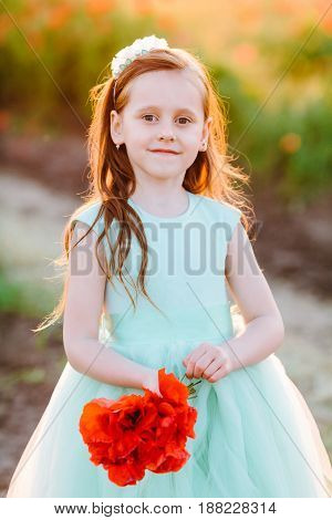 kids fashion, happy childhood, wedding, nature concept - portrait of young charming lady in turquoise dress with bright red poppies in her hand and flowing brown hair, she's standing in sunlight