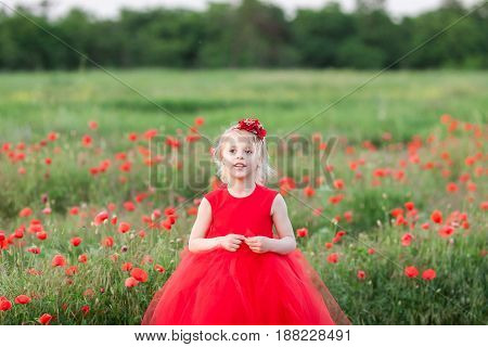 kid fashion, childhood, beauty, spring, holidays concept - beautiful little girl with blond hair and with flowers on it in gorgeous scarlet dress in the middle of poppy field. Space for the text.