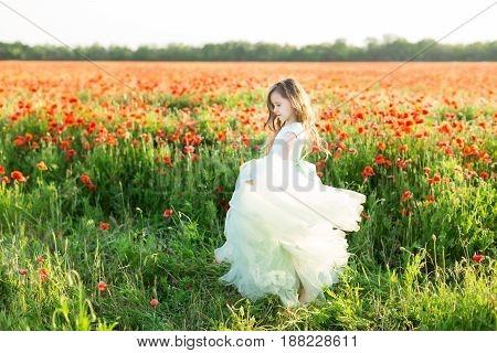 fairy tale, freedom, dancing, celebration, wedding, childhood, happiness concept - charming pug-nosed fairy in light blue dress with flying skirt spinning in the field of wild flowers