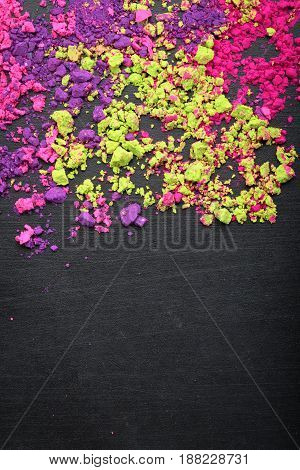 Makeup eyeshadows scattered on chalkboard background with copy space