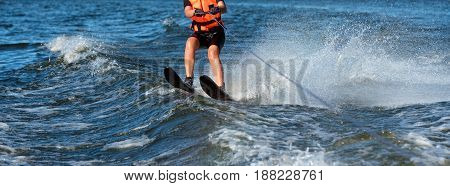 Woman riding water skis closeup. Body parts without a face. Athlete water skiing and having fun. Living a healthy lifestyle and staying active. Water sports theme. Summer by the sea. Banner for website.