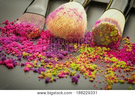 Close-up of make-up brushes on texture with colorful powder