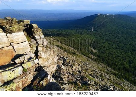 Travel to Ural mountains Russia. The view from a peak of a mountain on the valley with a forest and cloudy sky.
