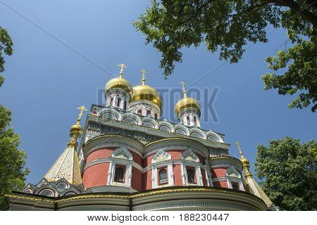 golden church dome on blue sky front view