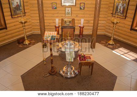 Dobrush, Belarus - May 20, 2017: The interior of the chapel with a font of bible and crucifix icons
