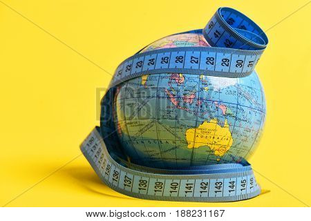 Measured geographical globe. Flexible ruler around Earth model isolated on warm yellow background