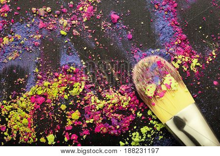 Top view of makeup brush on colorful background with makeup powder